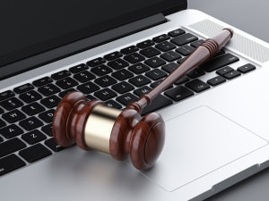 wooden gavel on laptop